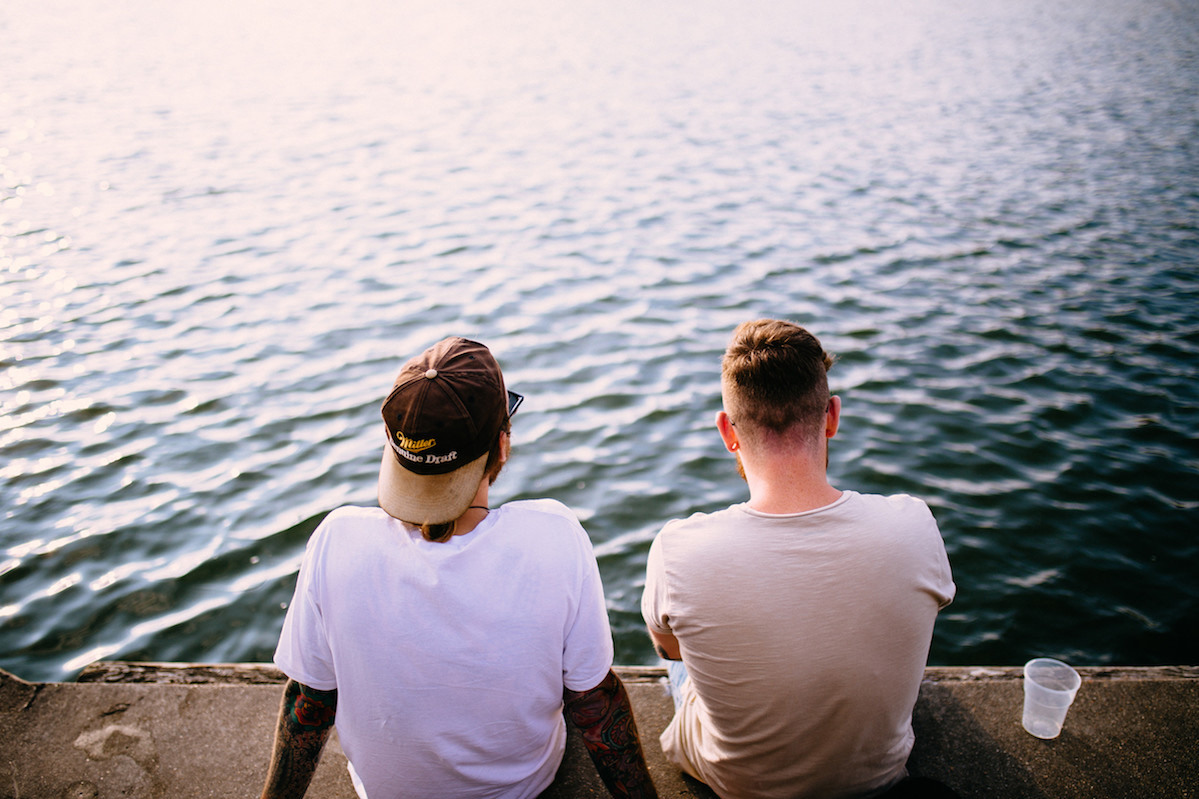 Two Millennials sitting by the water