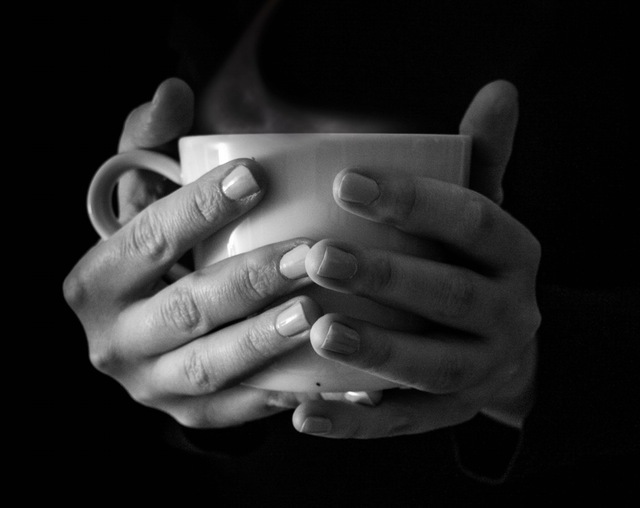 Person holding a mug of hot coffee