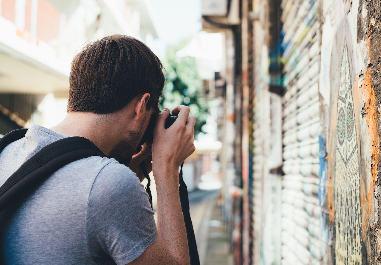 Man takes photo of street art