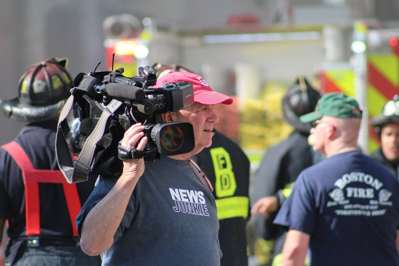 Man with video camera with firemen behind him