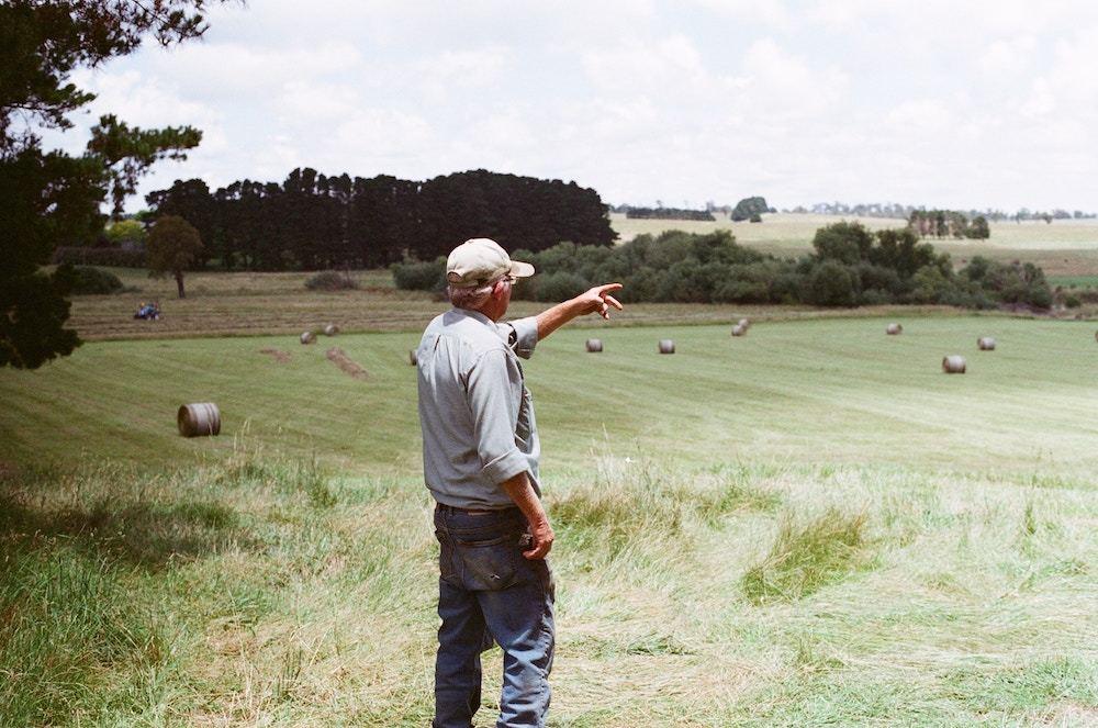 A farmer standing above fields