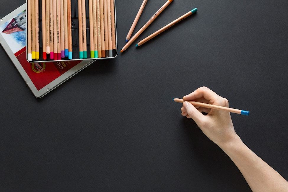 A hand holds a colored pencil, ready to begin drawing