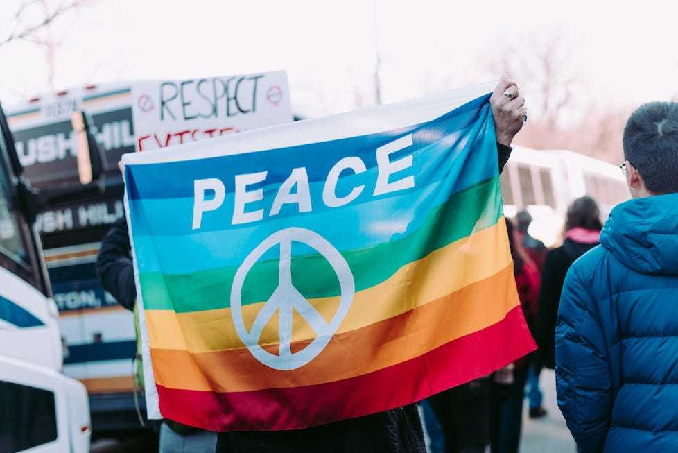 Protesters at a march holding up a rainbow flag with a peace sign on it.