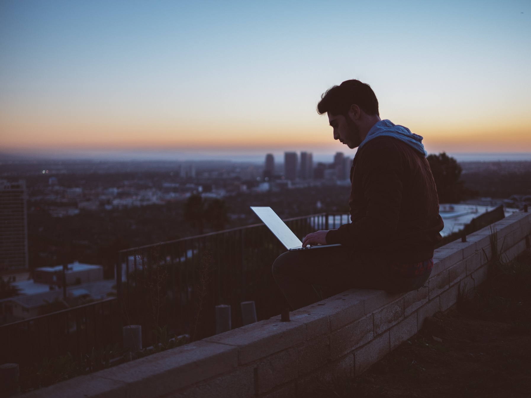 man on rooftop at sunset typing on computer