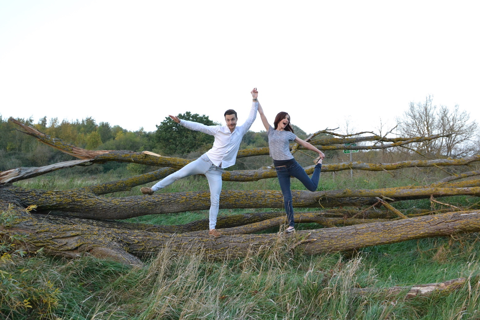 Man and woman striking silly pose by trees