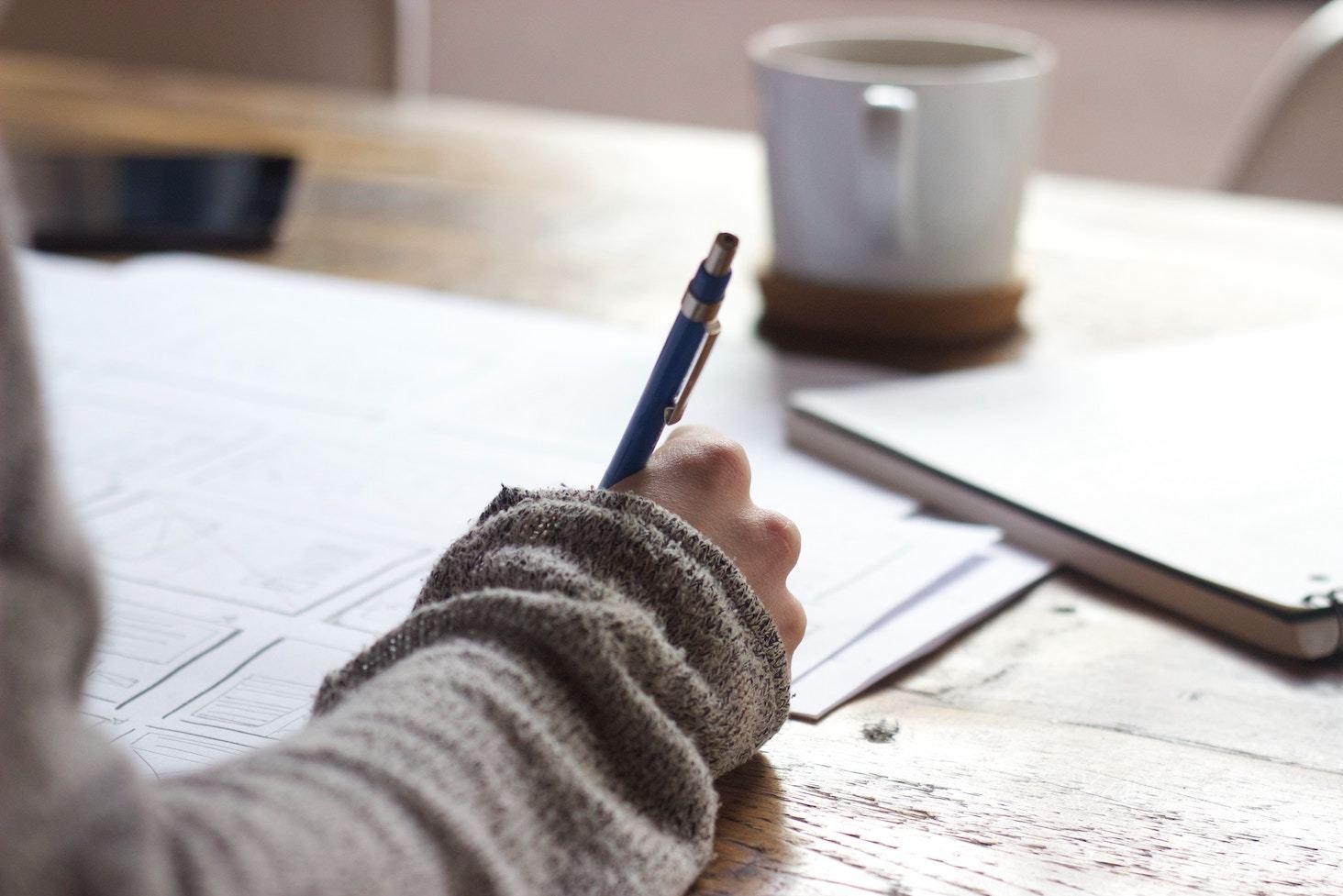 Hand holding pen at desk