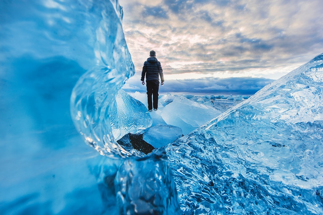 Image of a man standing on an ice formation and looking out