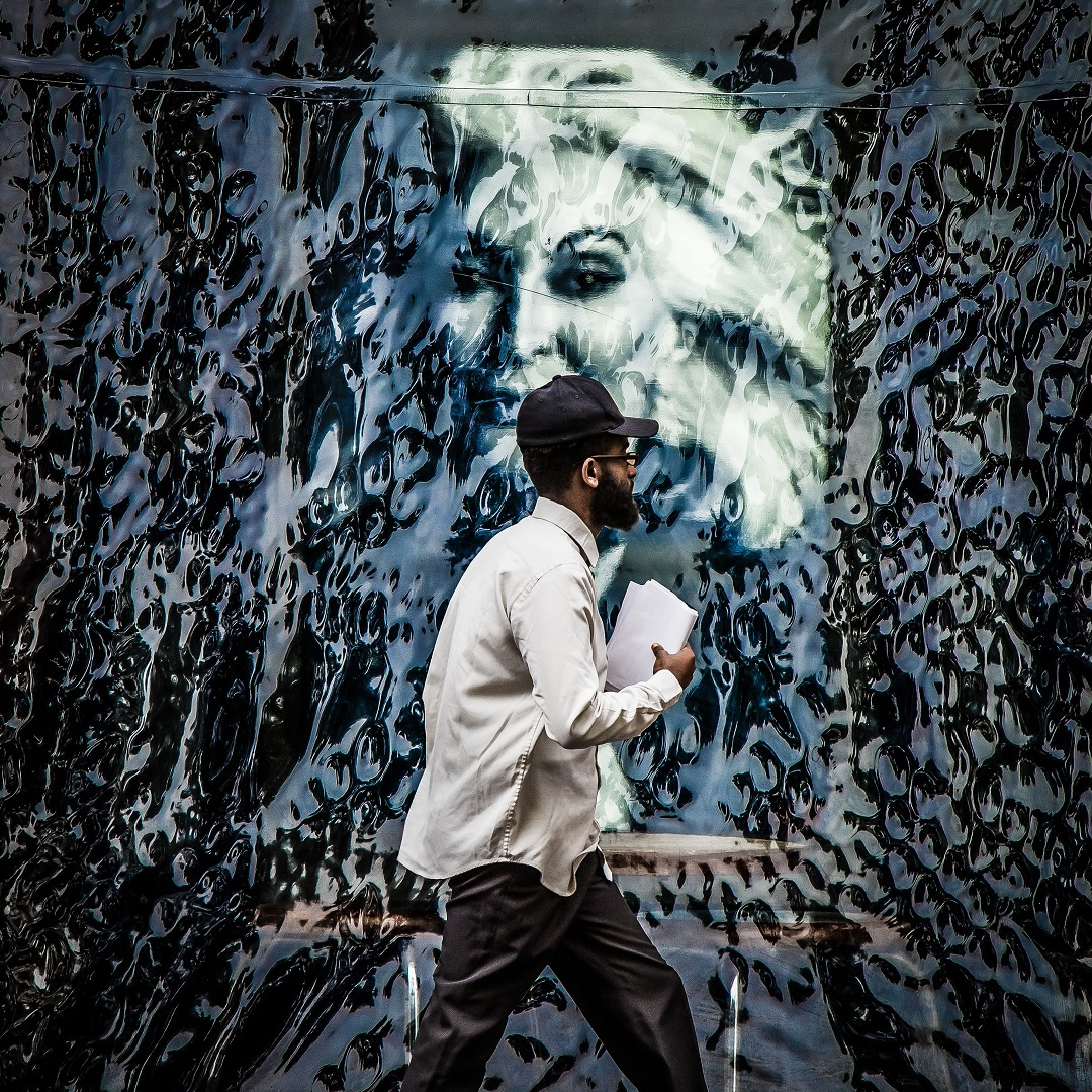 Man with papers walks past an elaborate mural