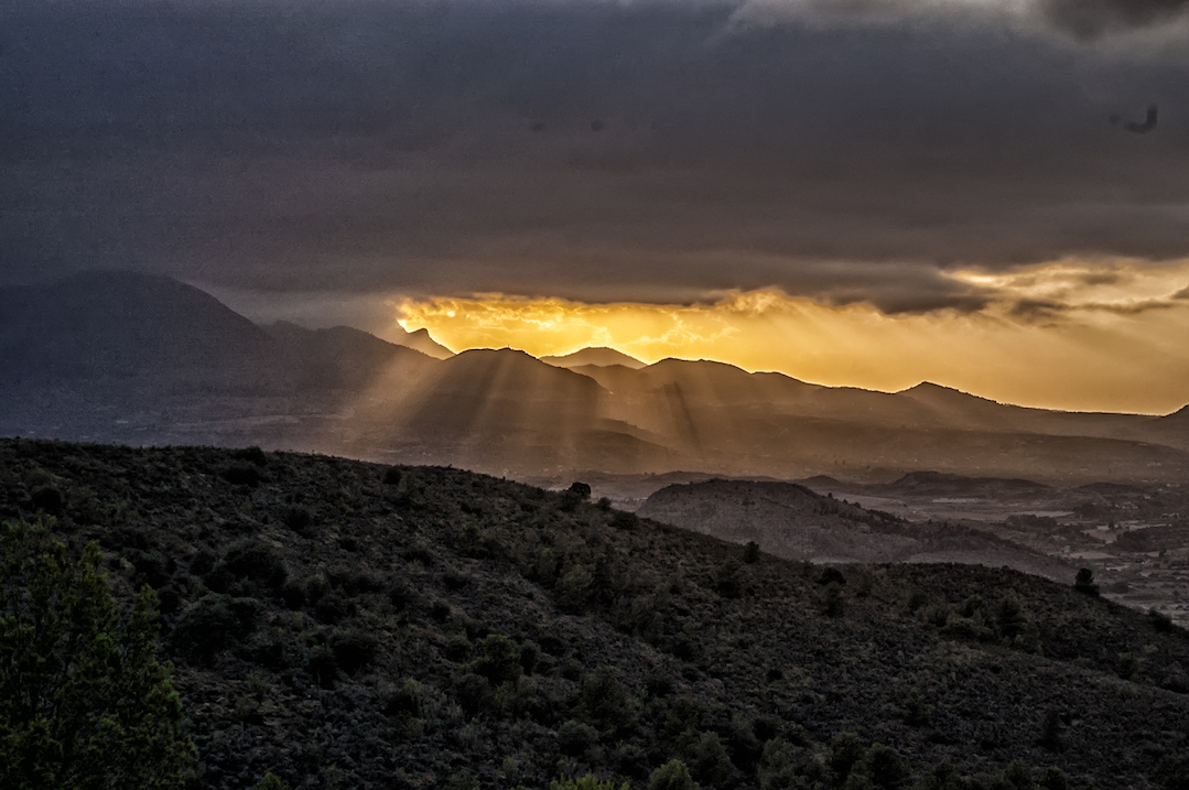 Sunrise breaking through the clouds over a mountain range