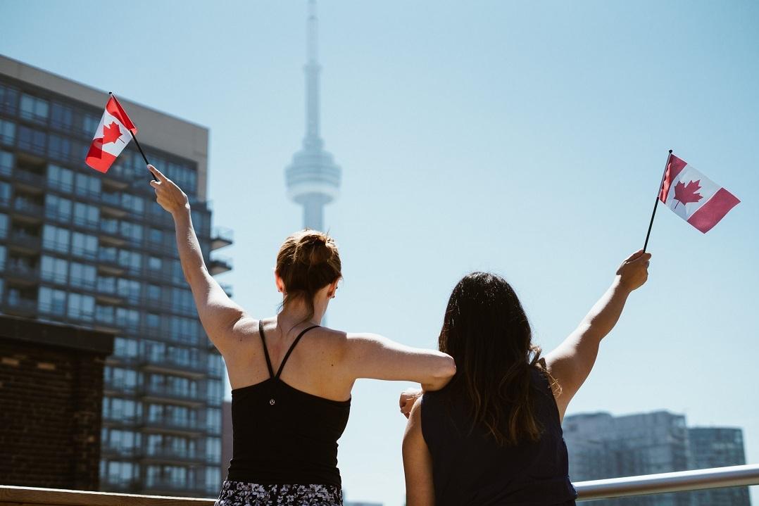 Two women waving Canadian flags