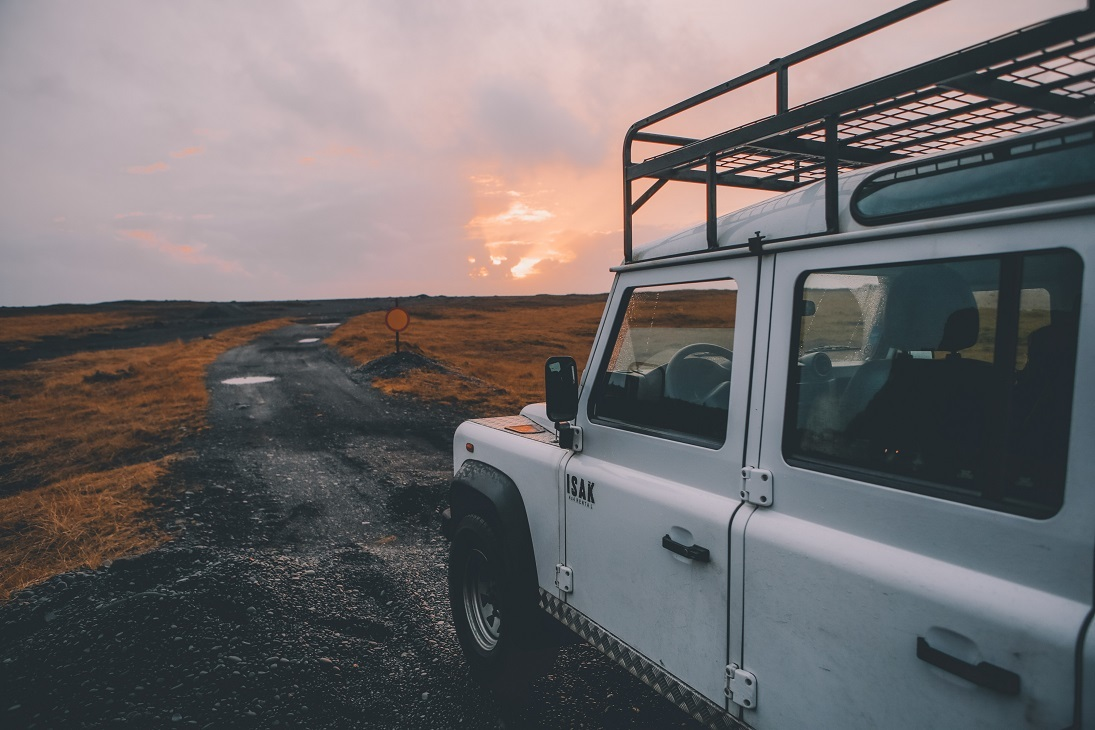 land rover on remote road with sunset in backdrop