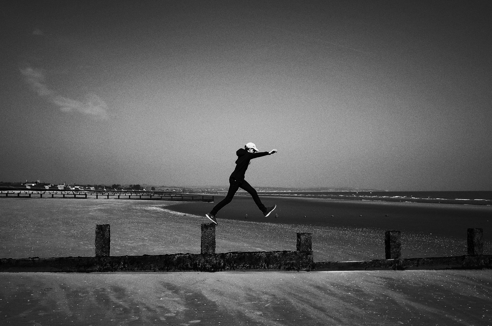 A man jumps along a pier on the shore
