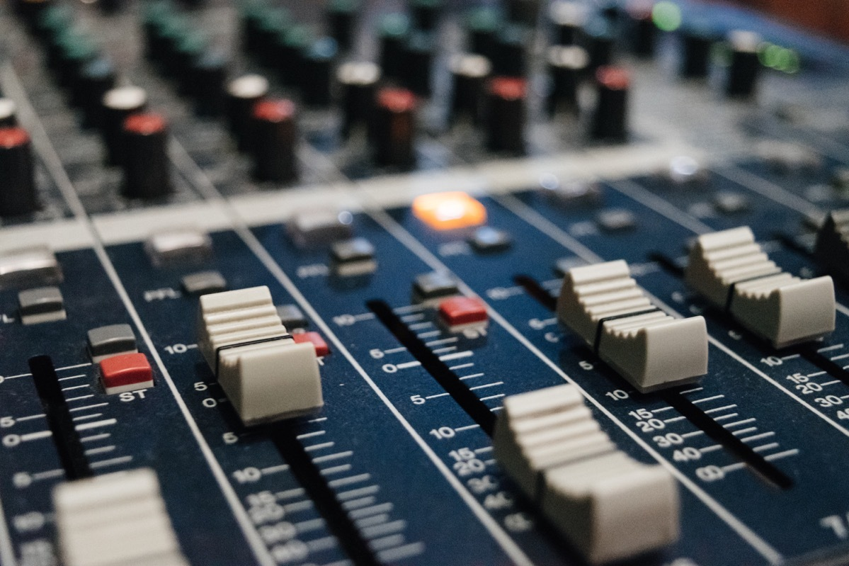 A close-up of an audio mixing board