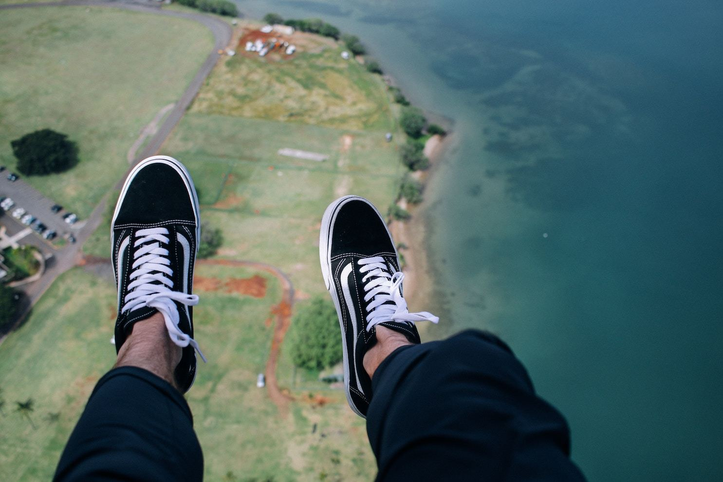 A man's legs, in baggy pants and sneakers, hang above the shoreline as seen from above