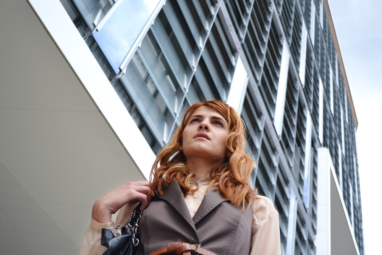 A woman in professional dress outside an office building, shot from below