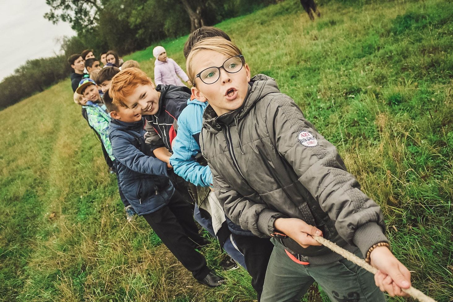 children play tug-of-war in a grassy field