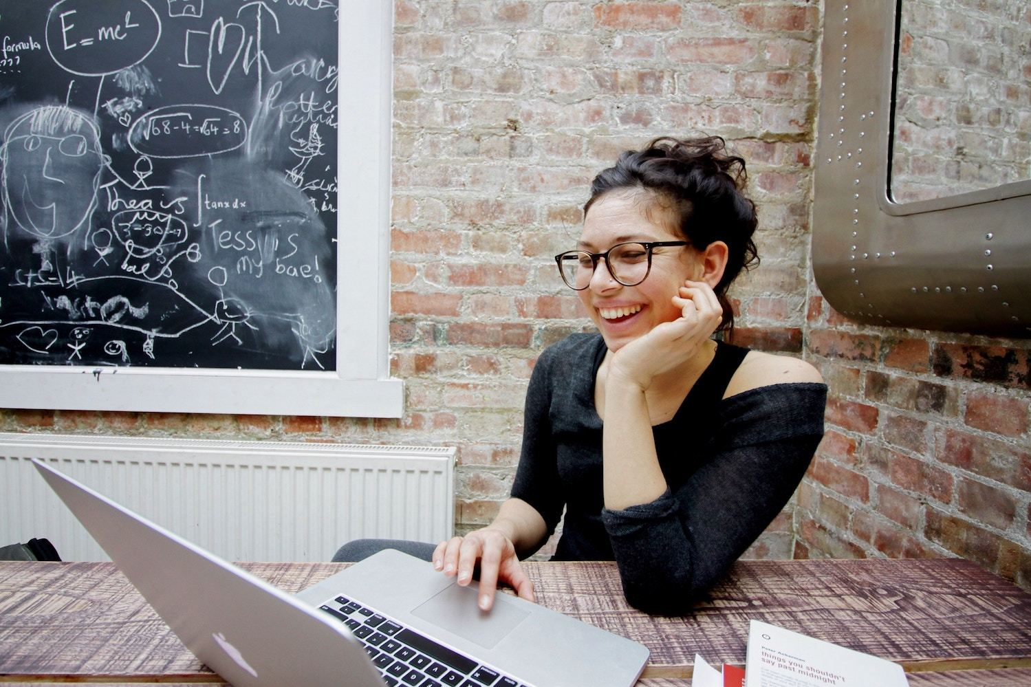 A young woman in glasses laughs while working on her laptop