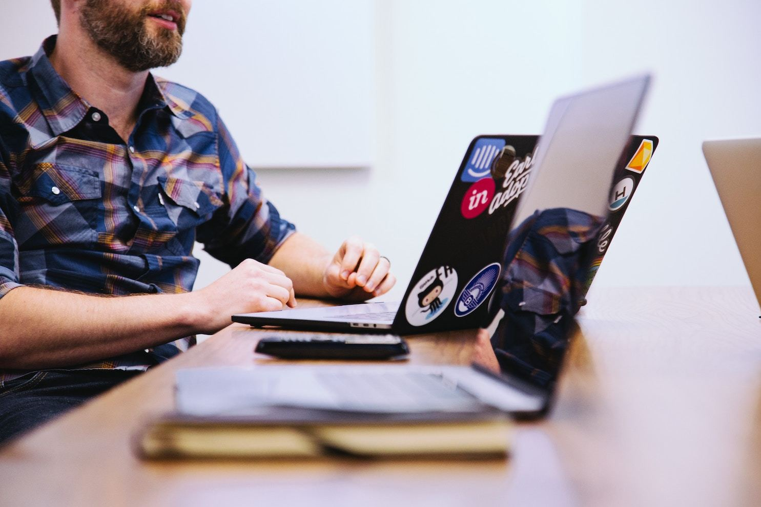 A bearded man in a flannel shirt with a sticker-covered laptop