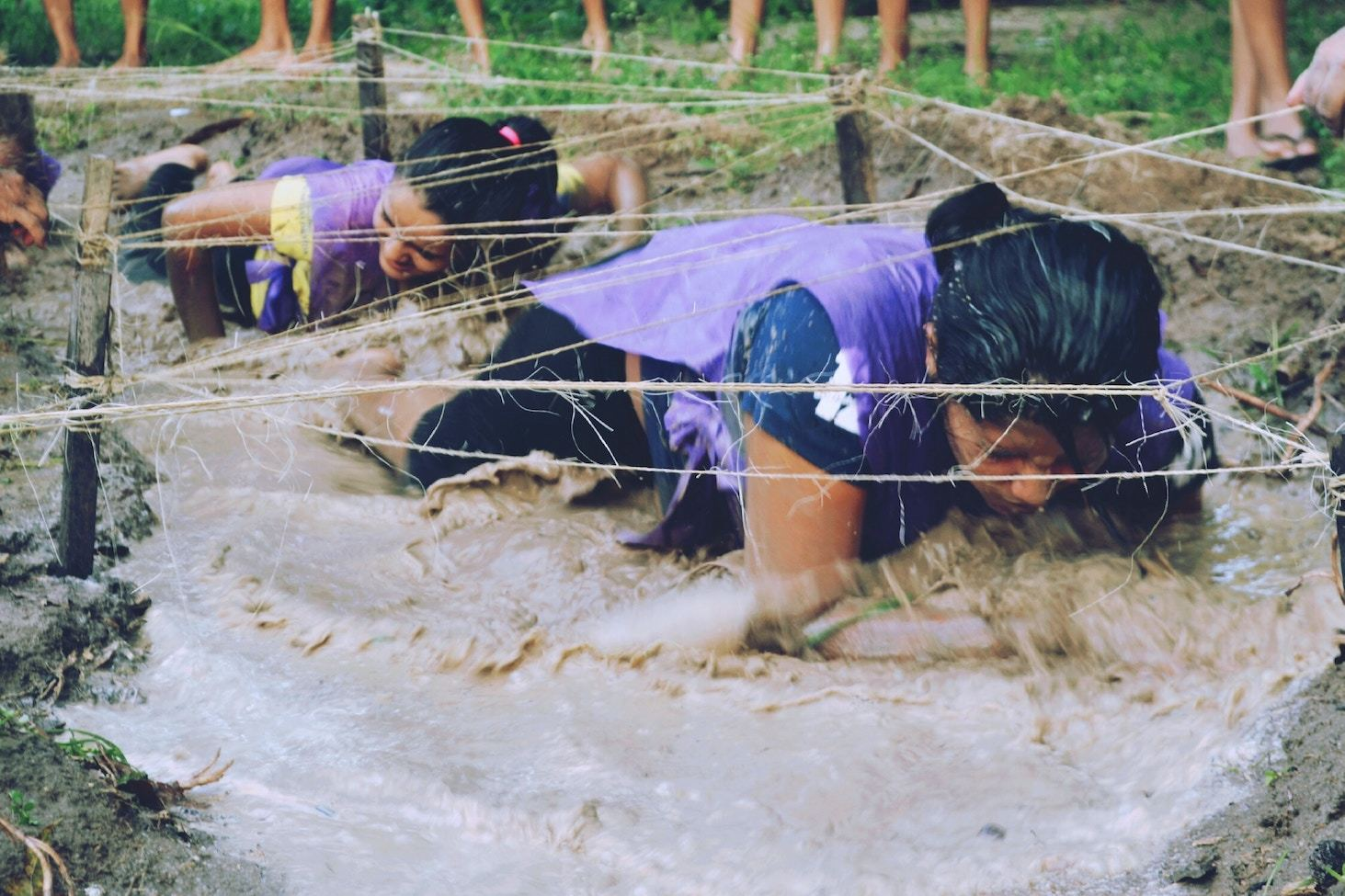 Women crawl through a muddy obstacle course