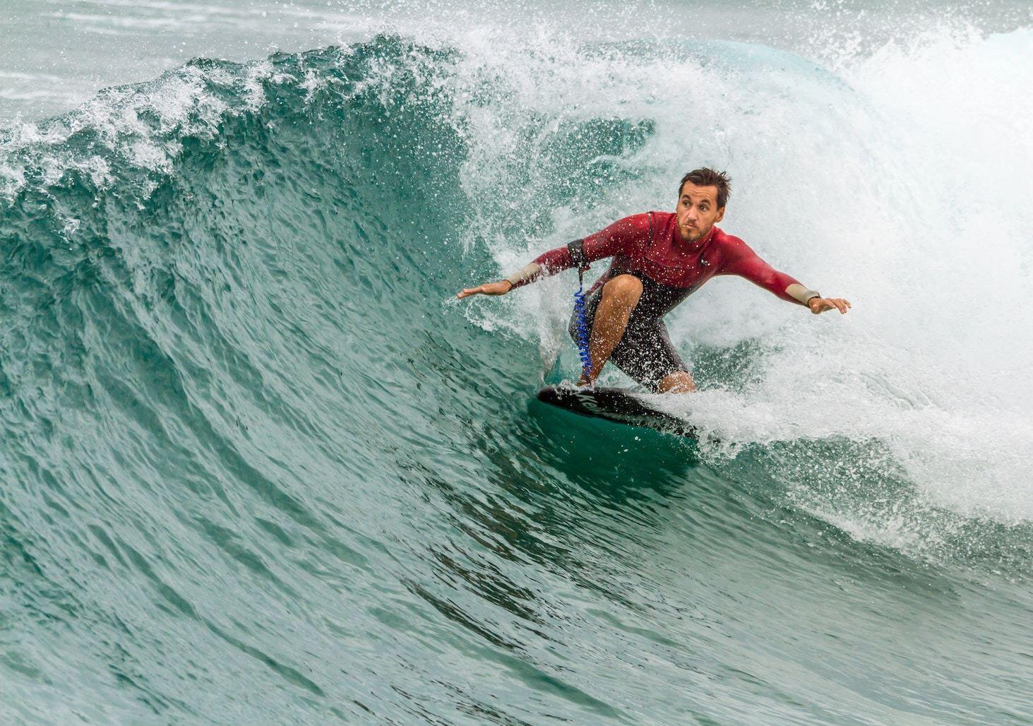 a man surfs in a red splashguard
