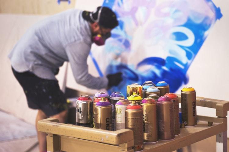 painter paints canvas, with cans of spray paint on a tray in the forefront