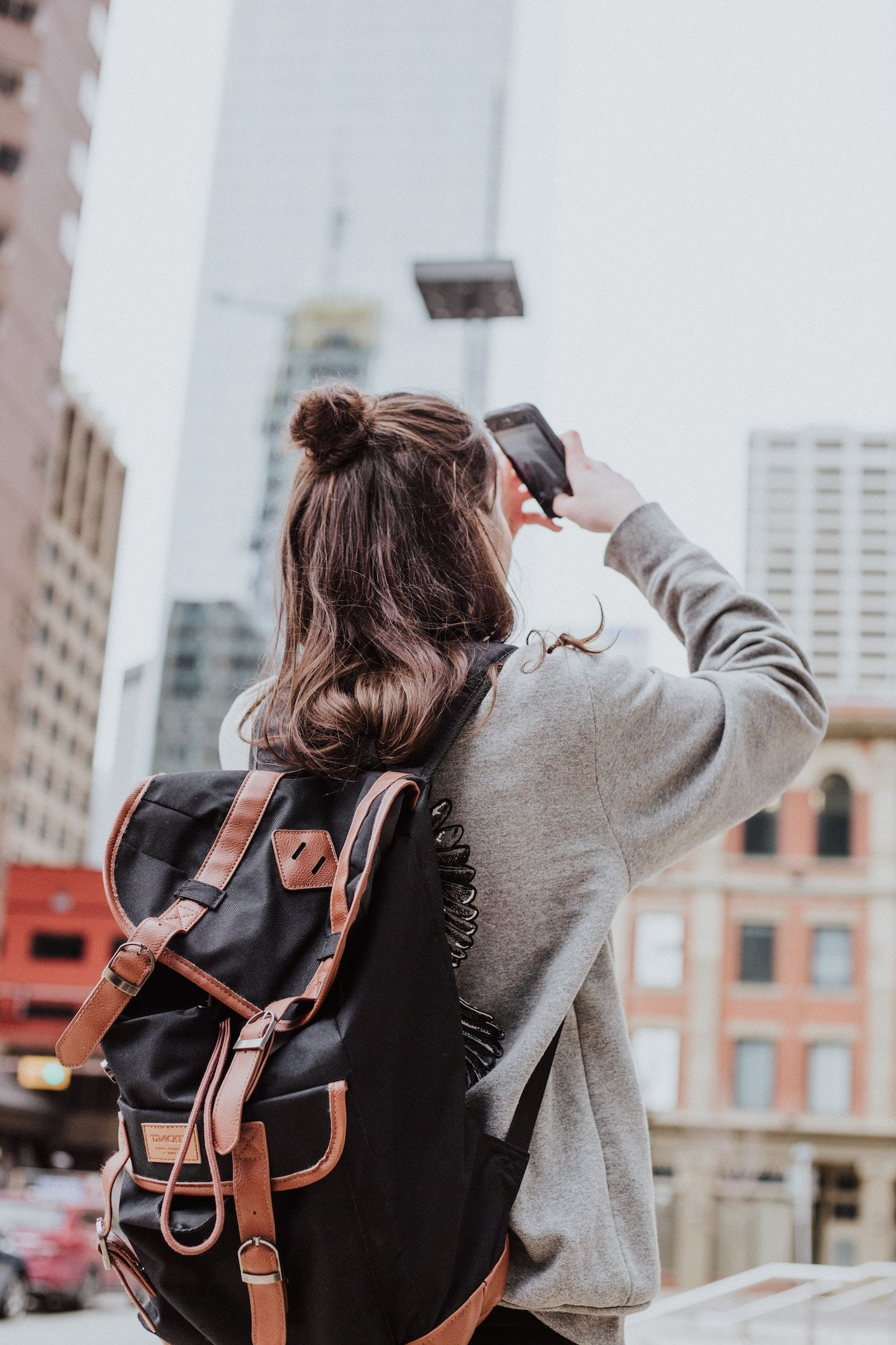 A young woman explores a city, taking pictures with her smartphone