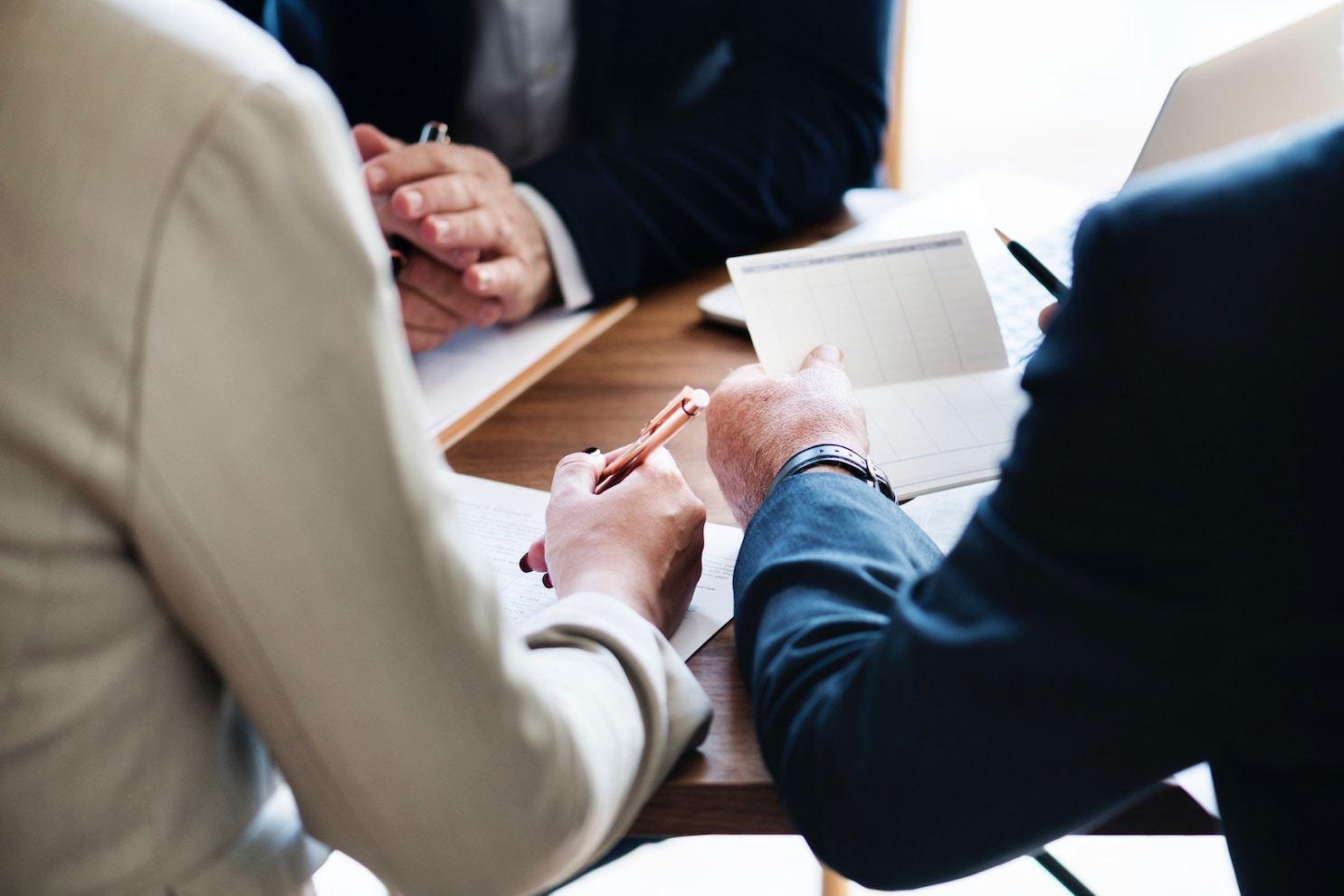 three businessmen converse around a table