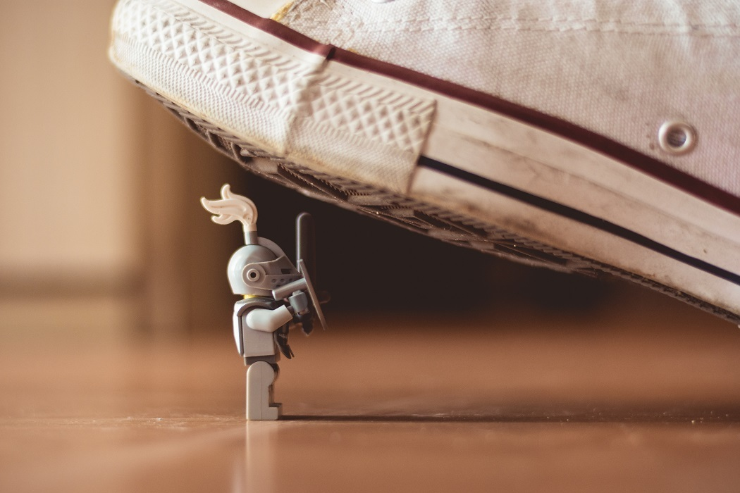 Macro shot of a shoe stepping on a small toy knight