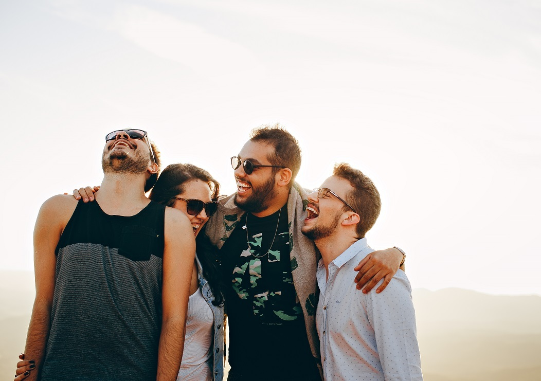 Four friends on a beach, laughing.
