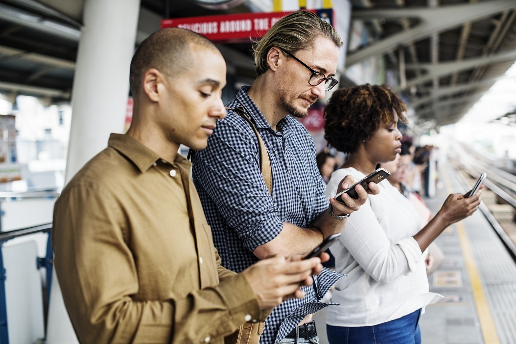 Three people stand side-by-side on a train platform while looking at their phones.