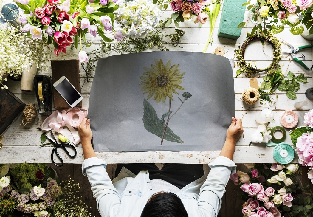 Top down shot of a person holding a large print of a sunflower