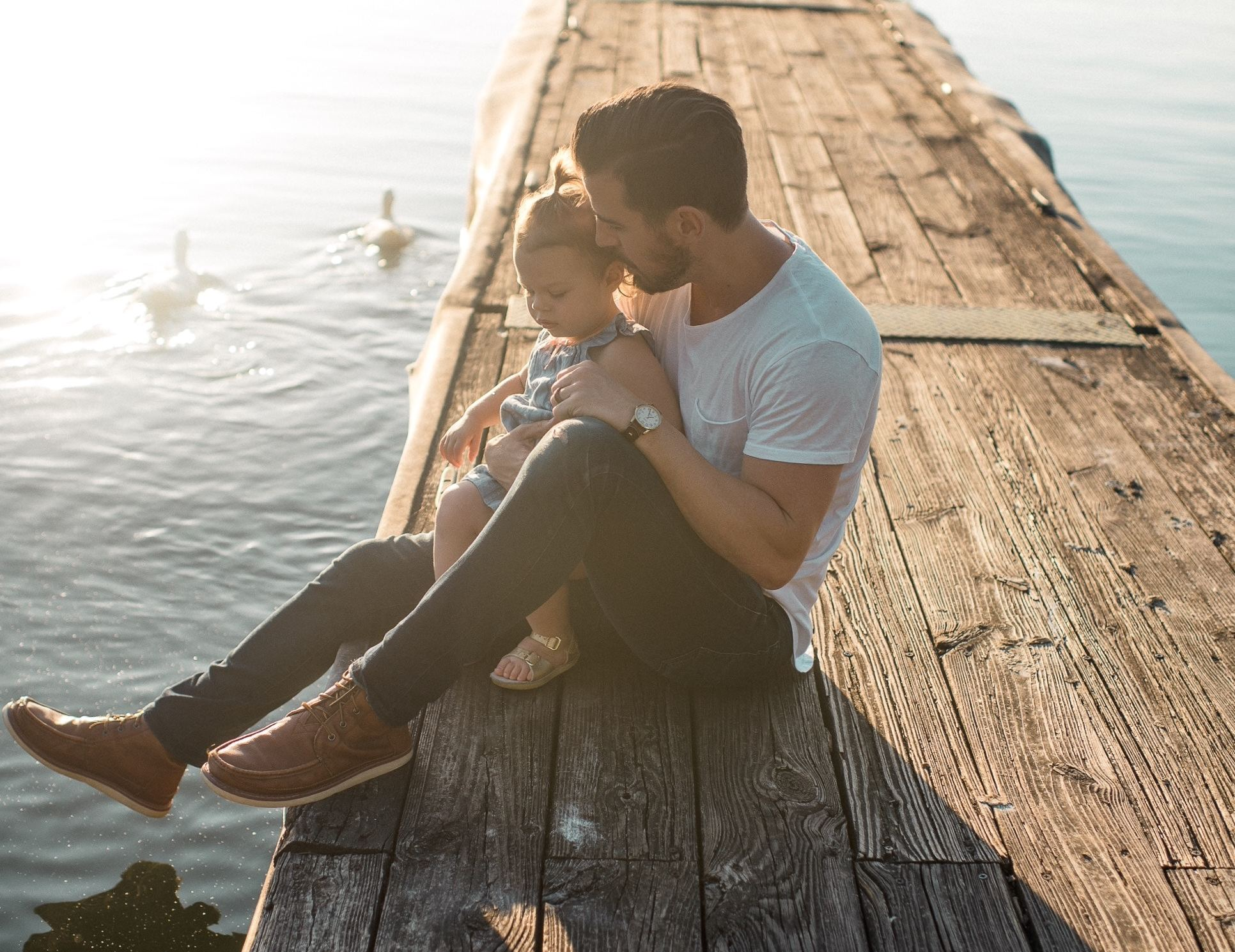 Father holding his daughter on a dock
