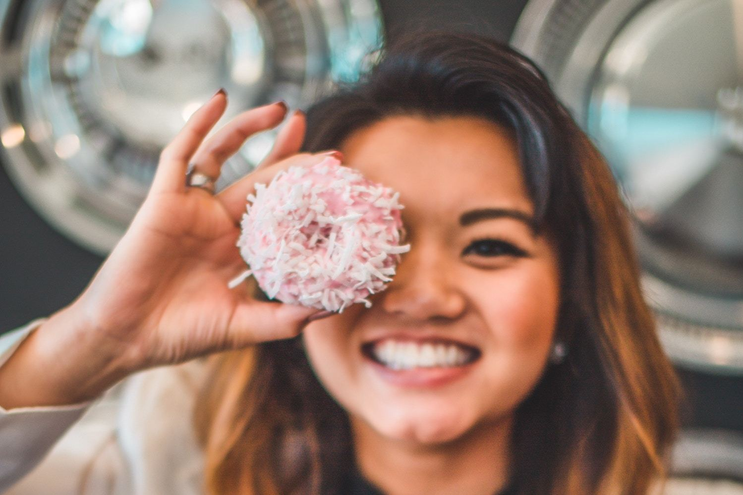 a woman poses with a pink donut