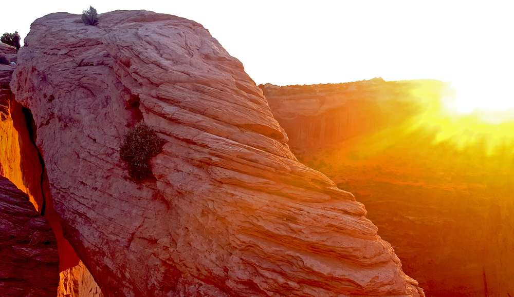 A dramatic view of the sunset over a rock arch in the desert
