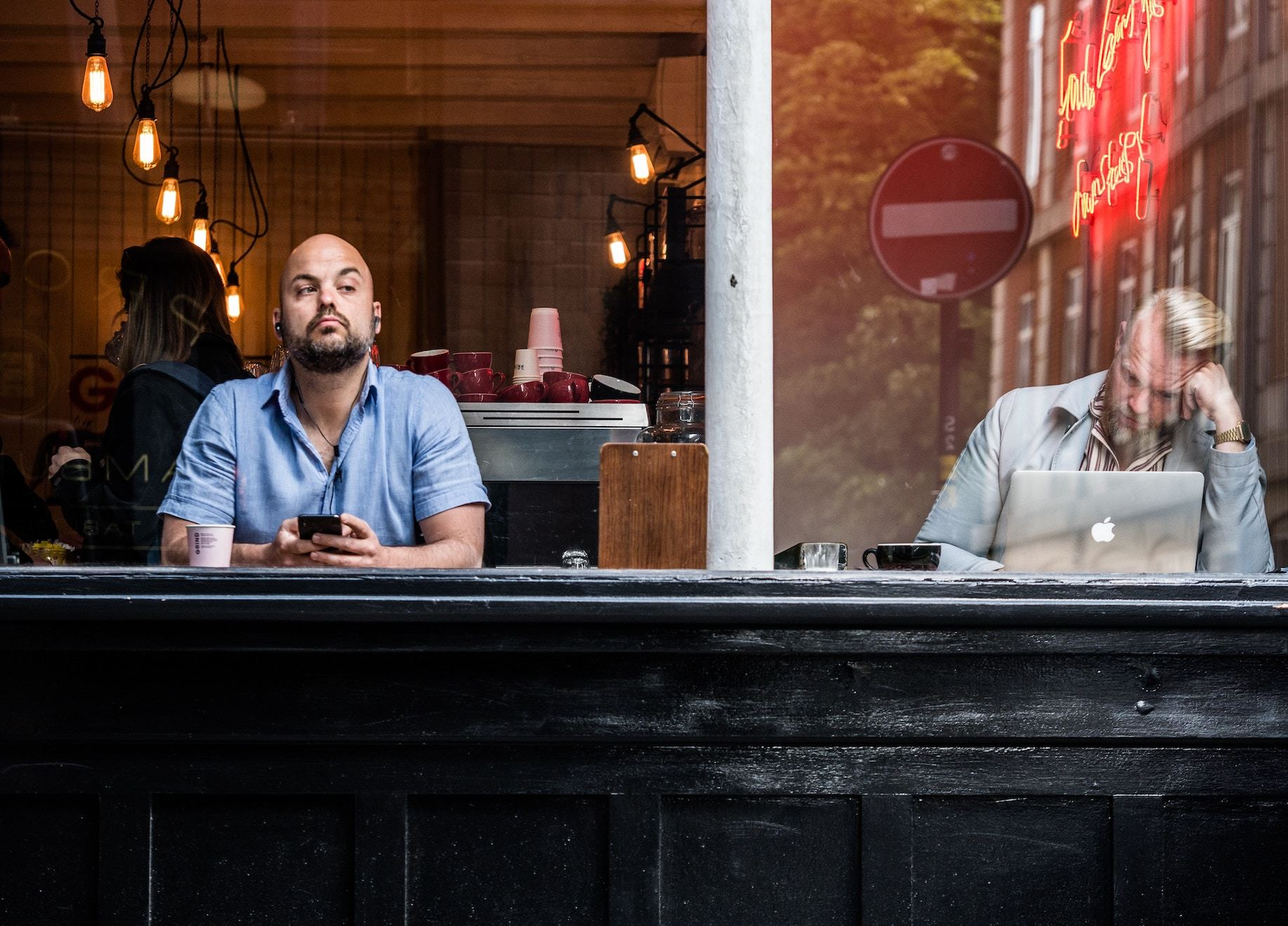 Two men at a cafe counter, one searches on laptop whiel the other looks out to the street
