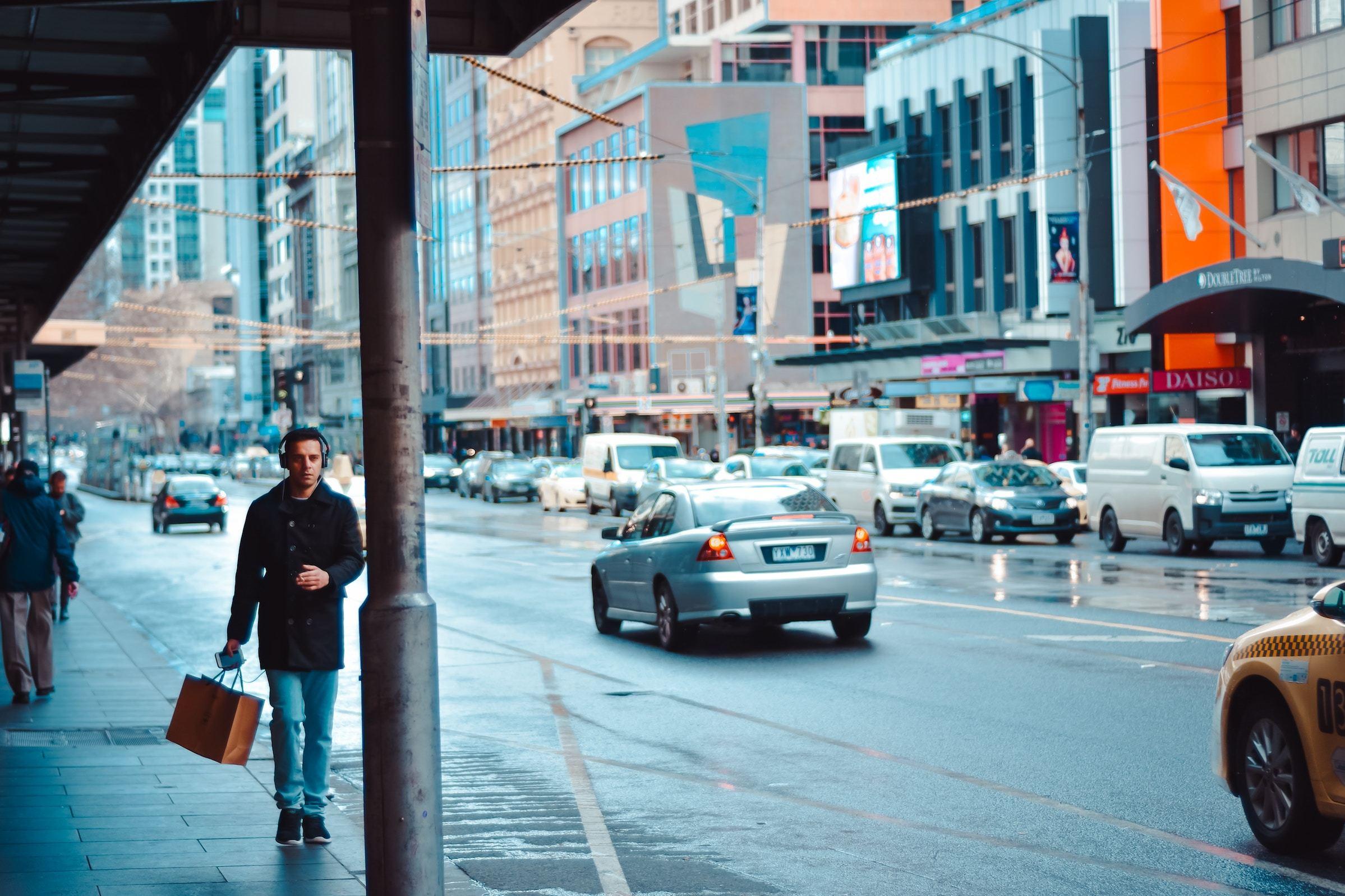 Man walking along street with shopping bag