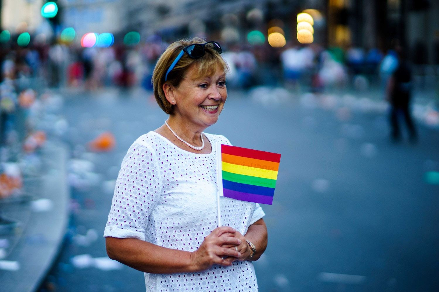 A woman holds a small rainbow flag in the aftermath of a parade