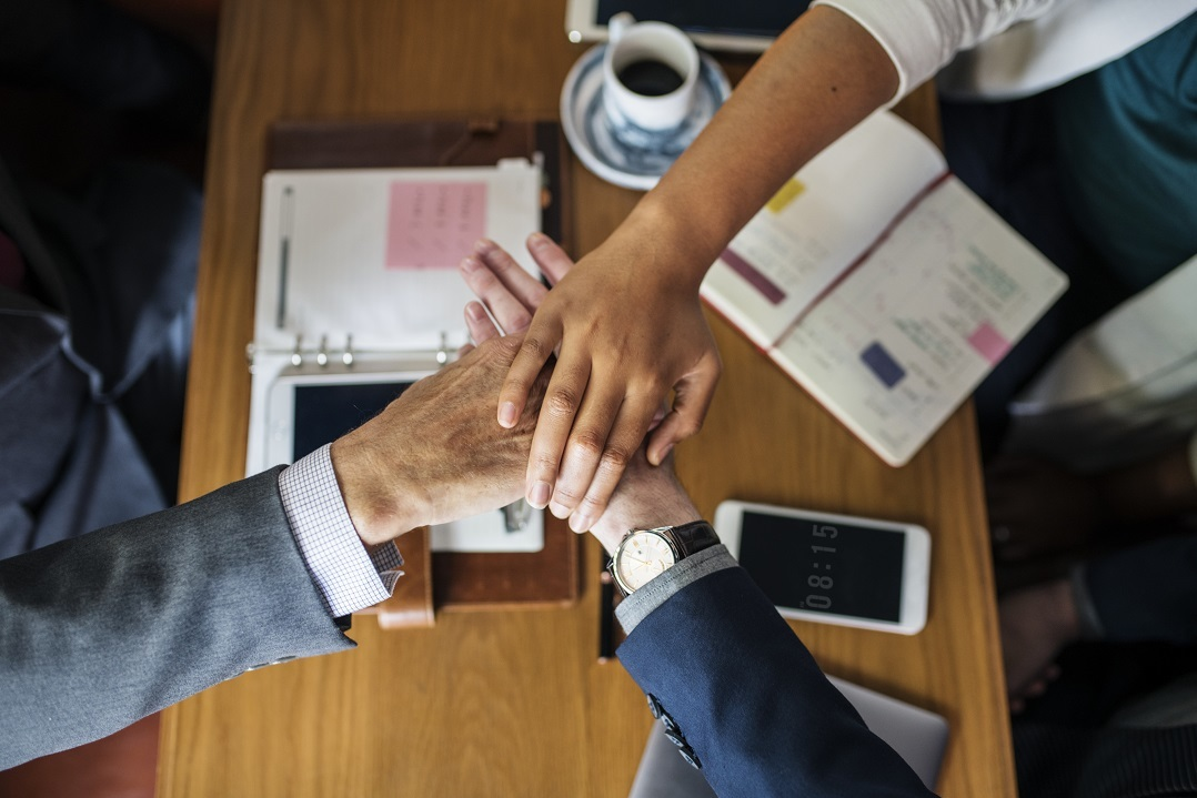 Team members put their hands in together over a conference room table.