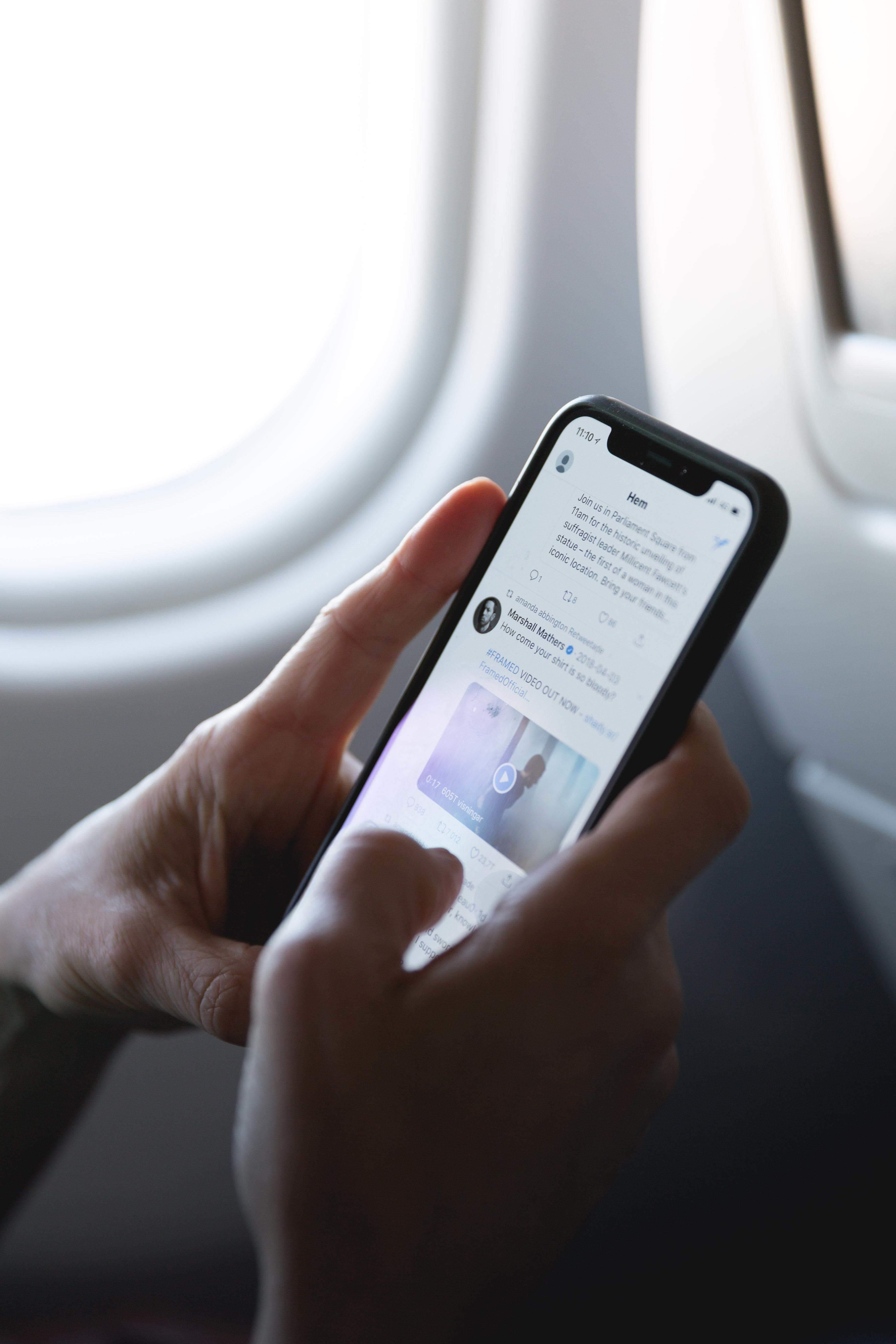man checks Twitter on plane