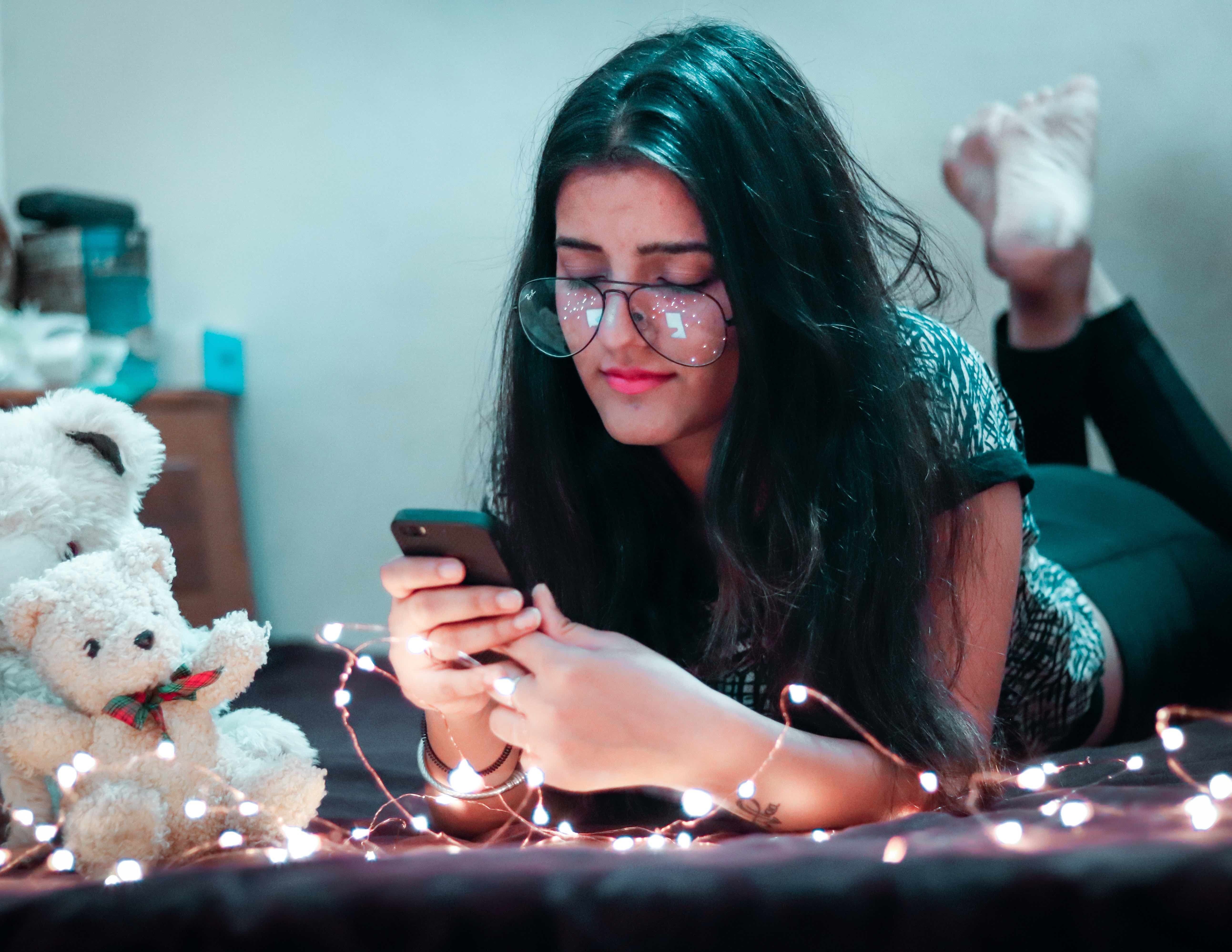 girl texting on bed