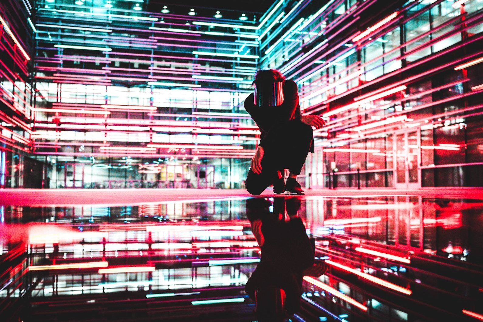 Person in black surrounded by neon
