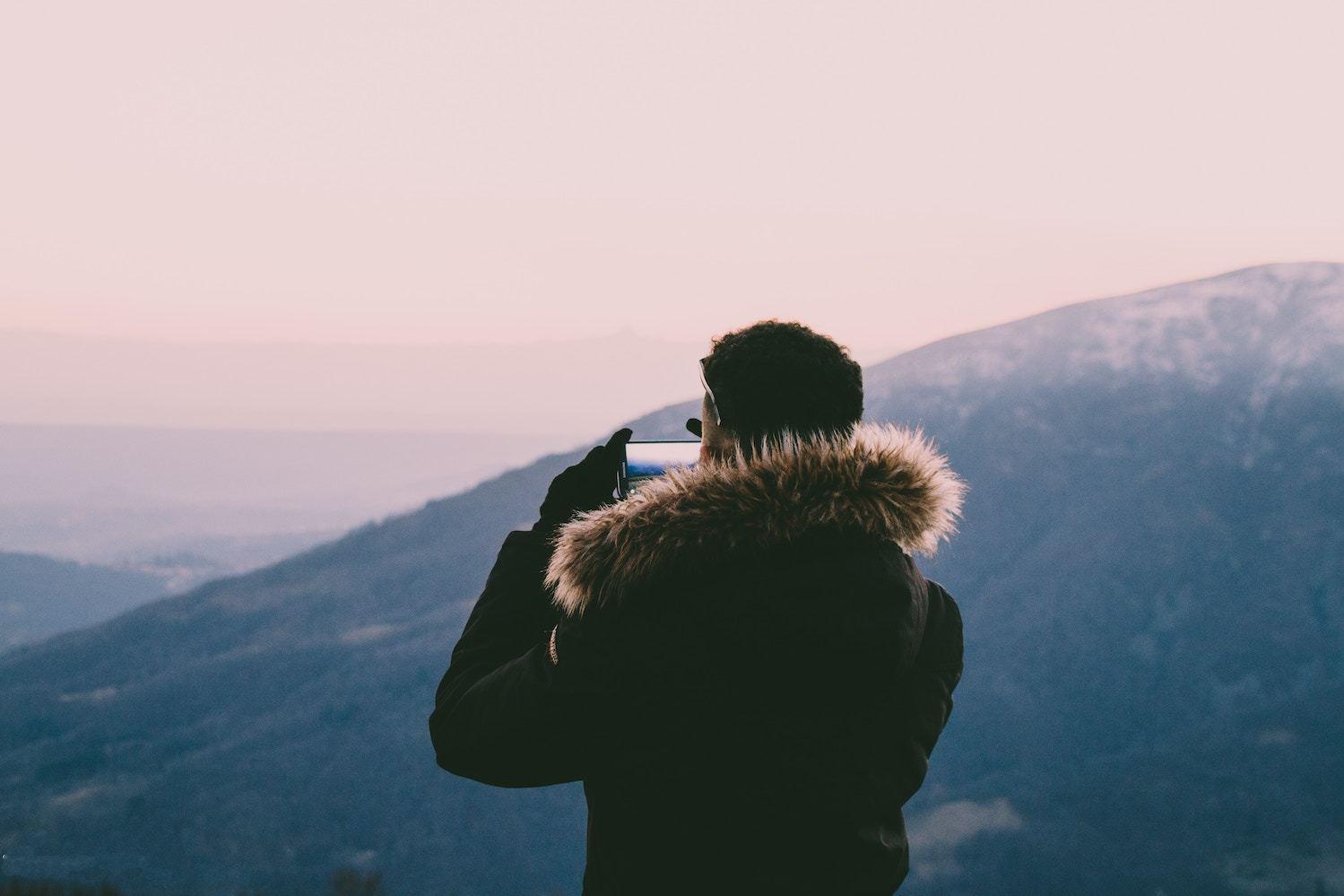 A man takes a photo from atop a mountain