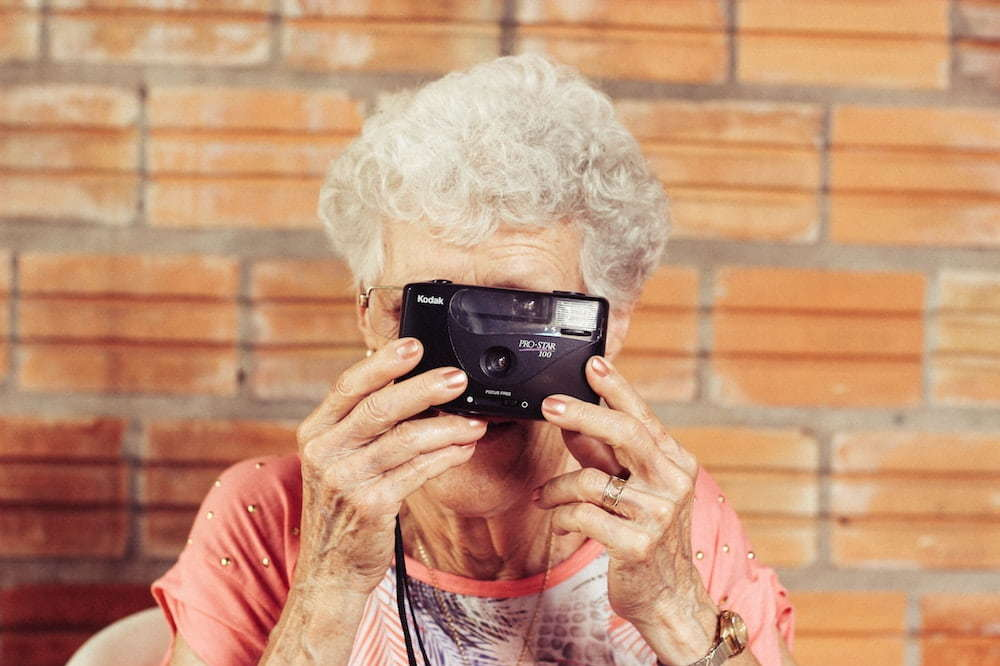Elderly woman holding a camera defies age-based market segmentation