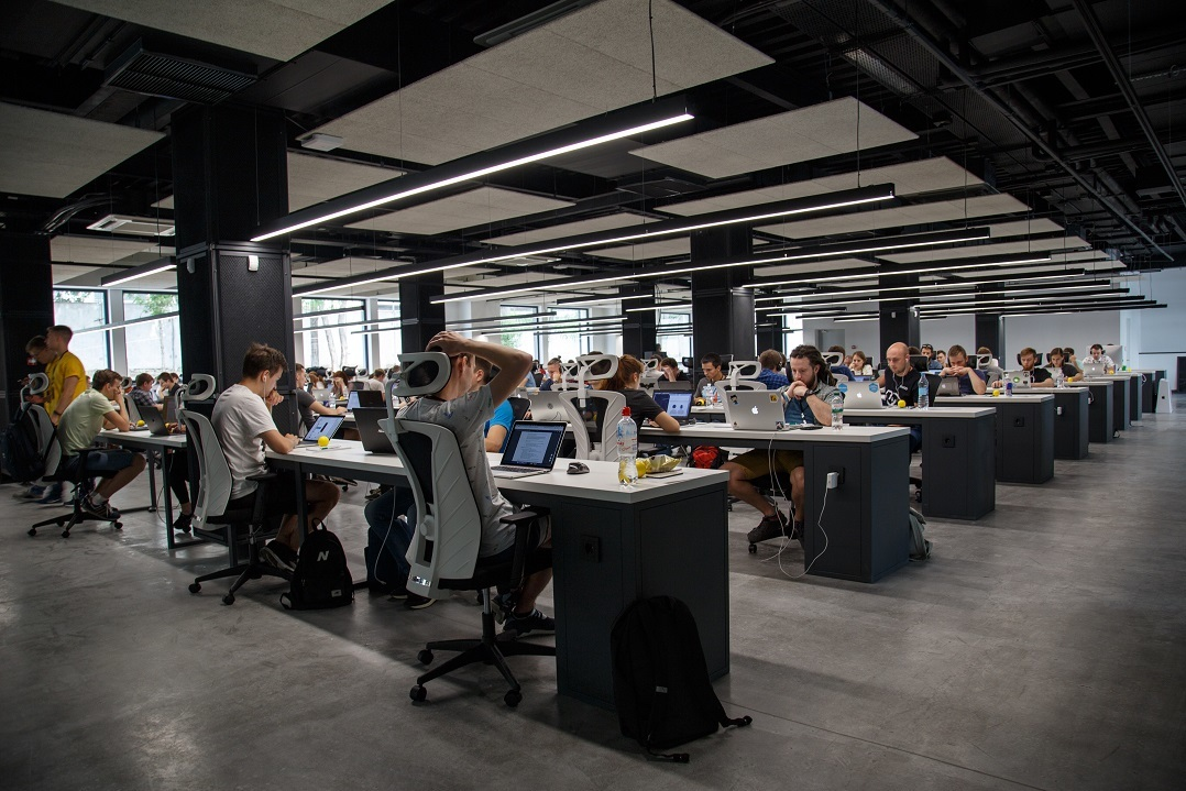 A large team of marketers works at desks with laptops