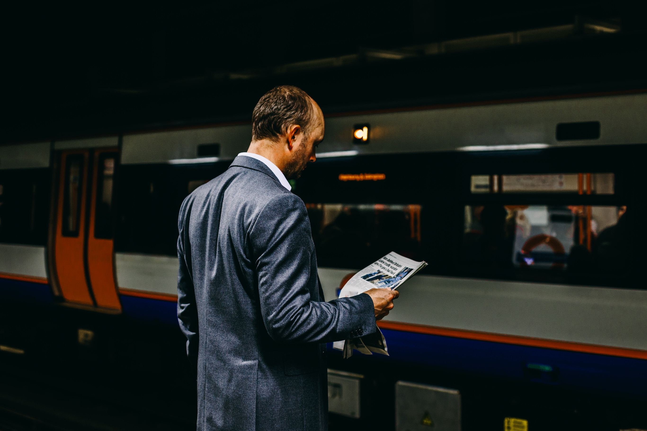 Man standing on train platform reading newspaper