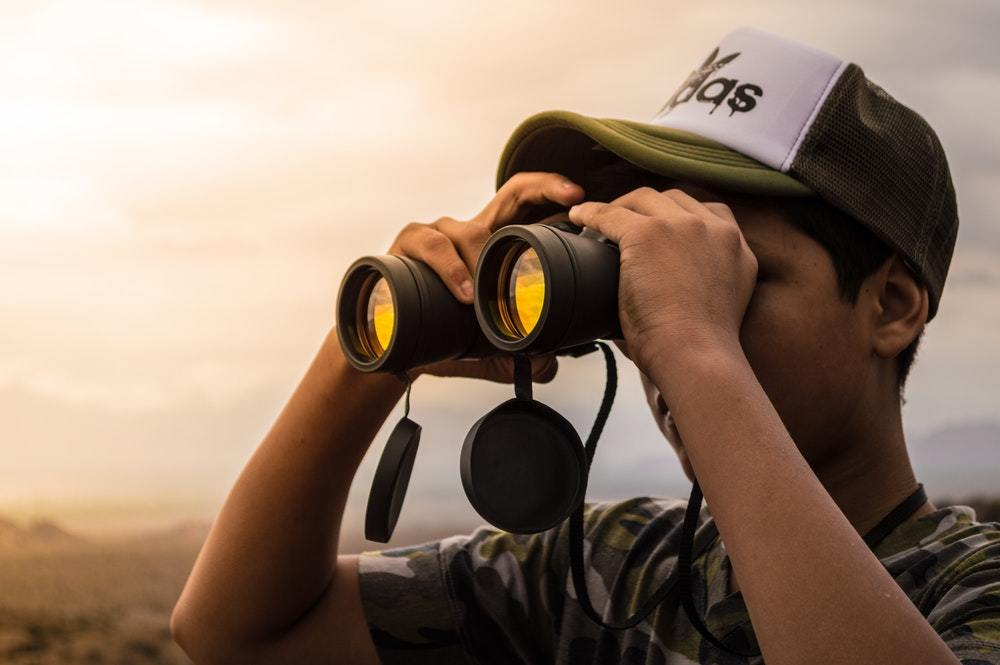 A man watches the scene at sunset through his binoculars.