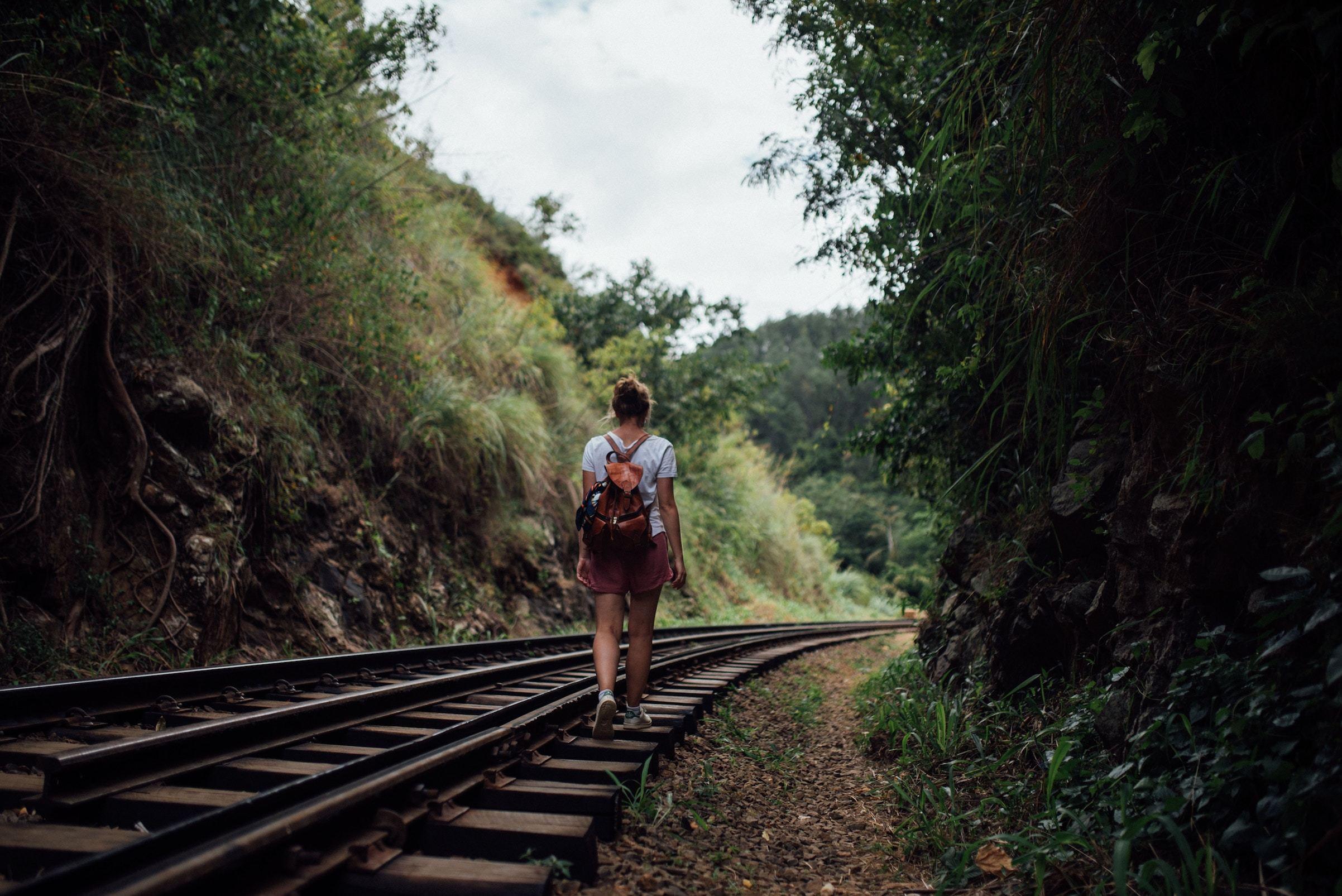 Woman walking along rural train tracks