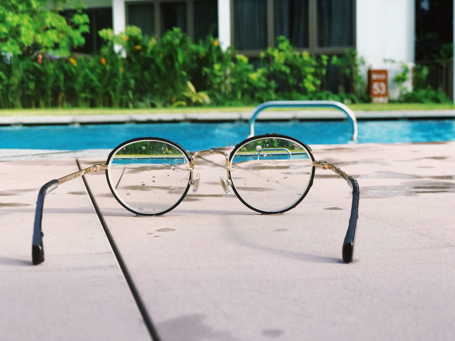 pair of glasses in front of pool