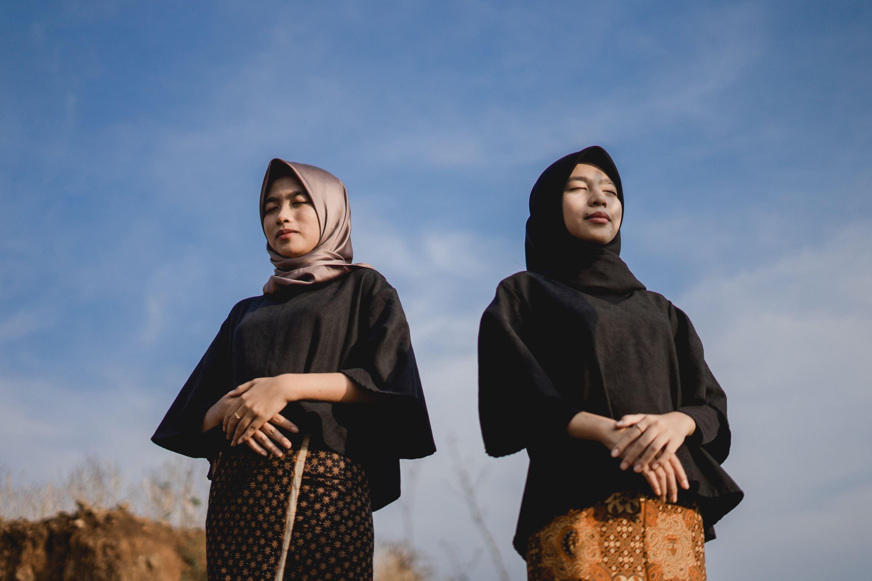 Two Muslim ladies with eyes closed