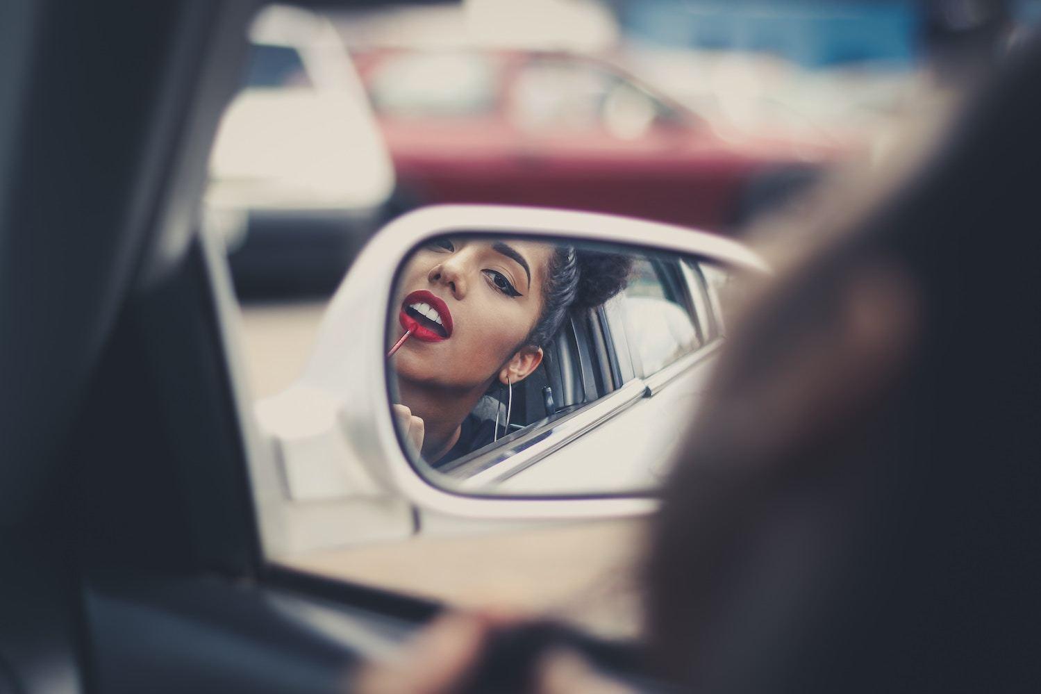 woman applies lipstick in car mirror